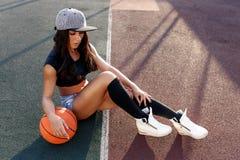 Mujer morena hermosa que juega a baloncesto en la corte al aire libre Fotografía de archivo