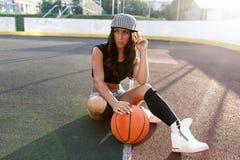 Mujer morena hermosa que juega a baloncesto en la corte al aire libre Foto de archivo