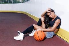 Mujer morena hermosa que juega a baloncesto en la corte al aire libre Fotos de archivo libres de regalías