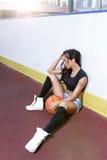 Mujer morena hermosa que juega a baloncesto en la corte al aire libre Imagen de archivo