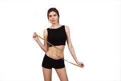 Mujer morena hermosa que mide su cintura con una cinta de la medida aislada en un fondo blanco Imagenes de archivo