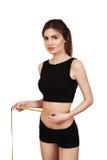 Mujer morena hermosa que mide su cintura con una cinta de la medida aislada en un fondo blanco Fotos de archivo libres de regalías