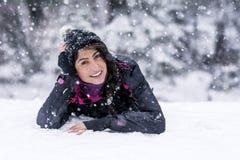 Mujer morena hermosa que miente en la nieve, gozando de la nieve del invierno Imagen de archivo