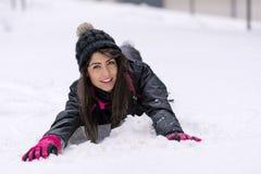 Mujer morena hermosa que miente en la nieve, gozando de la nieve del invierno Fotografía de archivo libre de regalías
