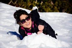 Mujer morena hermosa que miente en la nieve, gozando de la nieve del invierno Fotos de archivo