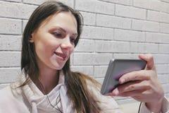 Mujer morena hermosa que mira seria romántico de un serial en auriculares en el teléfono móvil en una pared blanca del ladrillo imagenes de archivo