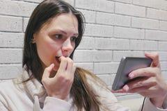 Mujer morena hermosa que mira seria terrible de un serial en auriculares en el teléfono móvil en una pared blanca del ladrillo fotos de archivo