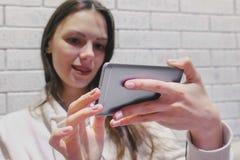 Mujer morena hermosa que mira un serial en auriculares en el teléfono móvil en un fondo blanco de la pared del ladrillo imagen de archivo