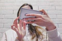 Mujer morena hermosa que mira un serial en auriculares en el teléfono móvil en un fondo blanco de la pared del ladrillo imágenes de archivo libres de regalías