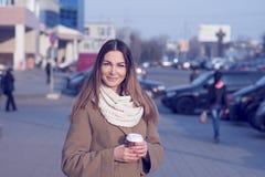 Mujer morena hermosa que sostiene un bolso y una taza de té o de café caliente, colocándose en la calle Fotografía de archivo libre de regalías