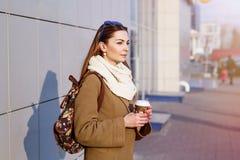 Mujer morena hermosa que sostiene un bolso y una taza de té o de café caliente, colocándose en la calle Imágenes de archivo libres de regalías