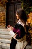 Mujer morena hermosa que usa el teléfono móvil al aire libre Imagenes de archivo