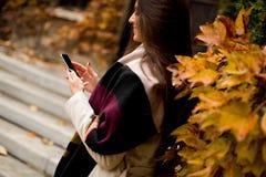 Mujer morena hermosa que usa el teléfono móvil al aire libre Imagen de archivo
