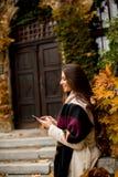 Mujer morena hermosa que usa el teléfono móvil al aire libre Fotografía de archivo