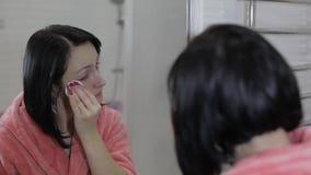 Mujer morena hermosa que usa los cojines de algodón Mujer que quita maquillaje almacen de metraje de vídeo