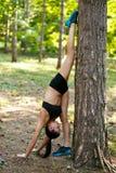 Mujer morena joven activa que hace ejercicios de la fuerza con las piernas encima de una cabeza abajo cerca de árbol en parque, e imágenes de archivo libres de regalías