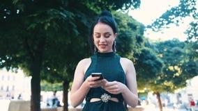 Mujer morena joven atractiva en ropa de sport negra que camina abajo de la calle, usando su teléfono, mirando alrededor y almacen de metraje de vídeo