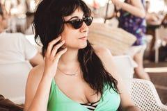 Mujer morena joven bonita con sentarse largo del pelo negro y de las gafas de sol pensativo imágenes de archivo libres de regalías