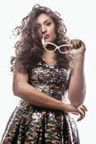 Mujer morena joven con el peinado rizado en el vestido de lujo del glamur aislado en gesticular blanco del fondo emocional Imagen de archivo libre de regalías