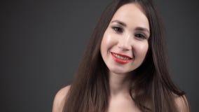 Mujer morena joven con el pelo brillante grueso largo Maquillaje perfecto metrajes