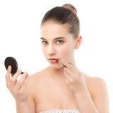Mujer morena joven con la cara limpia perfecta que aplica el lápiz labial usando el espejo Aislado en un blanco Fotos de archivo libres de regalías