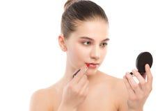 Mujer morena joven con la cara limpia perfecta que aplica el lápiz labial usando el espejo Aislado en un blanco Foto de archivo