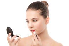 Mujer morena joven con la cara limpia perfecta que aplica el lápiz labial usando el espejo Aislado en un blanco Imagenes de archivo