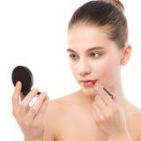 Mujer morena joven con la cara limpia perfecta que aplica el lápiz labial usando el espejo Aislado en un blanco Fotografía de archivo