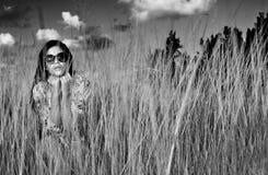 Mujer morena joven con las gafas de sol en campo de hierba - ennegrézcase y foto de archivo
