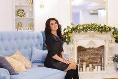 Mujer morena joven elegante que sonríe y que plantea sentarse en el sofá Imágenes de archivo libres de regalías