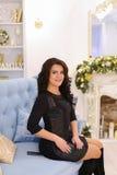 Mujer morena joven elegante que sonríe y que plantea sentarse en el sofá Fotos de archivo