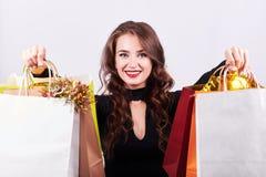 Mujer morena joven elegante que sostiene bolsos que hacen compras coloridos foto de archivo