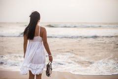 Mujer morena joven en el vestido blanco del verano que se coloca en la playa y que mira al mar muchacha que se relaja de vacacion imagen de archivo