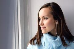 Mujer morena joven en suéter de lana azul que escucha la música en los auriculares vía un smartphone en el alféizar en el cuarto  Foto de archivo libre de regalías
