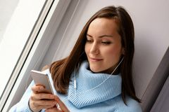 Mujer morena joven en suéter de lana azul que escucha la música en los auriculares vía un smartphone en el alféizar en el cuarto  Imagen de archivo