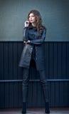 Mujer morena joven encantadora en equipo, capa y pantalones de cuero negros, con la pared gris oscuro en fondo Mujer magnífica at Fotos de archivo