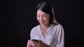 Mujer morena joven encantadora que mecanografía en el teléfono, colocándose aislado en el fondo negro, sonriendo en la cámara almacen de metraje de vídeo