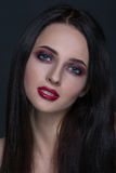 Mujer morena joven hermosa con el retrato perfecto del primer de la piel en fondo gris oscuro Peinado ondulado, maquillaje de luj fotos de archivo libres de regalías