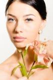Mujer morena joven hermosa con la piel perfecta, los ojos azules y el pendiente de lujo de la joyería sosteniendo la flor del lir Imagen de archivo