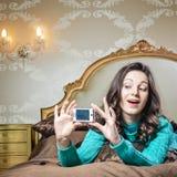 Mujer morena joven hermosa en cama que sonríe tomando un selfie Imágenes de archivo libres de regalías