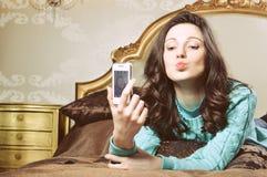 Mujer morena joven hermosa en cama que sonríe tomando un selfie Imagen de archivo libre de regalías