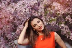Mujer morena joven hermosa en el prado con las flores blancas Imagenes de archivo