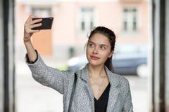 Mujer morena joven hermosa en la capa gris que toma un selfie con su smartphone en día nublado de la calle de la ciudad Imágenes de archivo libres de regalías