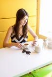 Mujer morena joven hermosa en un café del sitio Fotografía de archivo