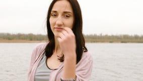 Mujer morena joven hermosa que se coloca delante del río en otoño metrajes