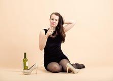 Mujer morena joven hermosa que sostiene un vidrio de vino blanco Imagenes de archivo