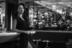 Mujer morena joven magnífica en vestido oscuro con el vino imagenes de archivo