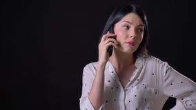 Mujer morena joven pensativa magnífica que habla en el teléfono, colocándose aislado en fondo negro metrajes