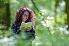 Mujer morena joven preciosa que lee un libro en un parque Foto de archivo