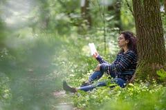 Mujer morena joven preciosa que lee un libro en un parque Fotos de archivo libres de regalías